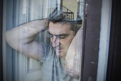 Close up portrait of sad and depressed 40s man looking through w. Indow glass reflection lonesome and thoughtful suffering depression thinking and feeling low in Royalty Free Stock Photo