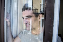 Close up portrait of sad and depressed 40s man looking through w. Indow glass reflection lonesome and thoughtful suffering depression thinking and feeling low in Stock Images
