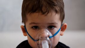Close up portrait of a sad little boy in a medical mask for inhalation.