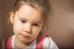 Close up portrait of sad little girl. Expressive little girl, melancholic, thinking away, studio shot on brown background Stock Photos