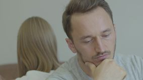 Close-up portrait of sad man and woman sitting back to back with unhappy faces at home. Problems in the relationship. Close up portrait of sad man and woman stock footage