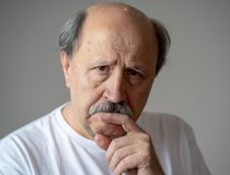 Close up portrait of sad old man face suffering from depression. Portrait of older adult senior man in pain with sad and exhausted face in human emotions facial royalty free stock photography
