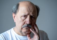 Close up portrait of sad old man face suffering from depression. Portrait of older adult senior man in pain with sad and exhausted face in human emotions facial royalty free stock photos
