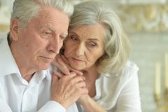 Close up portrait of sad senior couple at home. Close up portrait of beautiful sad senior couple posing at home royalty free stock photo