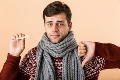 Close up portrait of a sad sick young man dressed in sweater. And scarf isolated over beige background, showing thermometer, thumbs down stock images