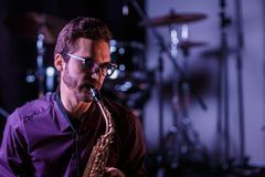 Close up portrait of saxophone player with drums on a background. Pink lighthning Stock Photography