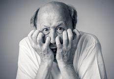 Close up of scared and shocked senior man gesturing in fear with hands and face. Close up portrait of a scared frightened old man in expression of fear in human stock photography