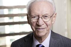 Senior Businessman Portrait. Close-up portrait of a senior businessman (in his 80's) smiling to the camera wearing a suit and tie, as well as old fashion glasses Royalty Free Stock Photos