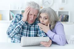 Close-up portrait of a  senior couple. With newspaper  at home Royalty Free Stock Photos