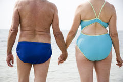 Close up portrait of a senior couple hand in hand walking in the sea Stock Photography