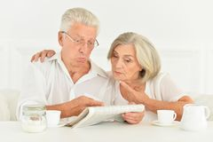 Close-up portrait of a senior couple with newspaper royalty free stock images