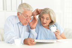 Close-up portrait of a senior couple with newspaper stock photography