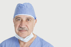 Close-up portrait of senior male surgeon over gray background Royalty Free Stock Photography