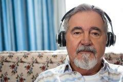 Close up portrait of senior man wearing headphones in nursing home. Close up portrait of senior man wearing headphones on sofa in nursing home Royalty Free Stock Image