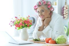 Portrait of senior woman in bathrobe with curlers sitting at table with laptop. Close up portrait of senior woman in bathrobe with curlers sitting at table with royalty free stock images