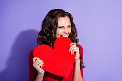 CLose up portrait of sensual attractive curly hairdo hairstyle s. He her girl holding large paper heart card in hands biting it with hate negativity stock photo