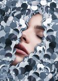 Sensual beautiful womans face among stock of shiny fashion sequins. Close-up portrait of a sensual beautiful womans face among stock of shiny fashion sequins in Royalty Free Stock Photography