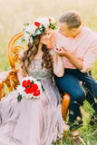 Close-up portrait of sensual beautiful young blonde woman and handsome man holding her hand sitting in chair outdoors Royalty Free Stock Photography