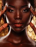 Portrait of sensual young african woman against golden background. Close up portrait of sensual young african woman against golden background Royalty Free Stock Photos