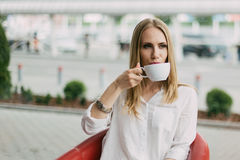 Close-up portrait of the serious blonde woman drinking cup of tea in the cafe. Stock Photography