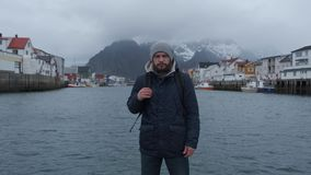 Close up portrait of serious man of Norway pier, background boat stock video