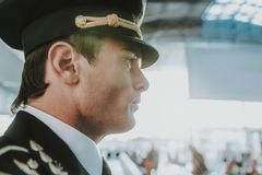 Handsome young pilot standing in the airport royalty free stock image
