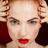 Close-up portrait of european young woman model with glamour make-up and red bright manicure. christmas makeup, bloody red li Royalty Free Stock Photos