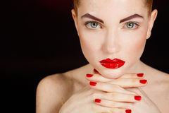 Close-up portrait of european young woman model with glamour make-up and red bright manicure. christmas makeup, bloody red li Stock Image