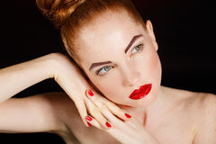 Close-up portrait of european young woman model with glamour make-up and red bright manicure. christmas makeup, bloody red li Stock Photos