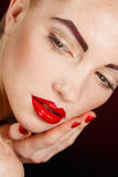 Close-up portrait of european young woman model with glamour make-up and red bright manicure. christmas makeup, bloody red li Royalty Free Stock Image