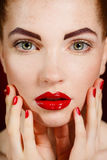 Close-up portrait of sexy european young woman model with glamour make-up and red bright manicure. christmas makeup, bloody red li Royalty Free Stock Image