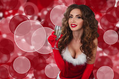 Close-up portrait of sexy woman in christmas dress with glass of champagne and looking at camera. Stock Image