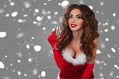 Close-up portrait of sexy woman in christmas dress on the grey background with glass of champagne and looking at camera. Royalty Free Stock Photography