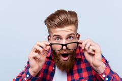 Close up portrait of shocked amazed man in checkered shirt touch. Ing his glasses stock photography