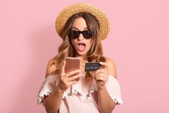 Close up portrait of shocked emotional attractive female with wide opened mouth, posing  over pink background in studio,. Holding credit card and smartphone in royalty free stock photography