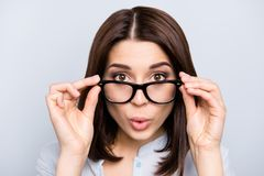 Close up portrait of shocked, impressed, pretty, charming, cute, successful, professional girl looking out glasses, holding stock photos