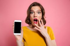 Close up portrait of a shocked young woman. Showing blank screen mobile phone isolated over pink background Stock Photos
