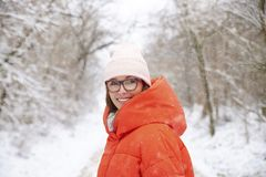 Woman walking outdoor in winter. Close-up portrait shot a happy woman wearing hat and warm coat while standing outdoor and enjoy winter weather stock image