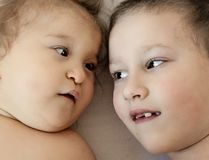 Close-up portrait of siblings lying on bed. Boy loves his disabled younger brother. -  image royalty free stock photography