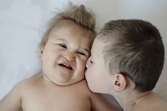 Close-up portrait of siblings lying on bed. Older boy kisses his disabled younger brother on cheek royalty free stock images