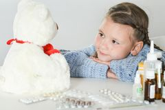 Close-up portrait of sick girl with white teddy bear at home. Portrait of sick girl with white teddy bear at home royalty free stock photography