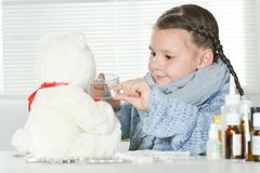 Close up portrait of sick girl with white teddy bear at home. Portrait of a sick girl with white teddy bear at home stock image