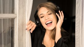 Close up portrait of a singing woman in headphones. She sing early in the morning at home. Close up portrait of a singing woman in headphones. She sing early in Stock Photo