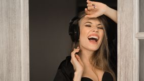 Close up portrait of a singing woman in headphones. She sing early in the morning at home. Close up portrait of a singing woman in headphones. She sing early in Royalty Free Stock Photos