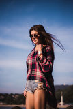 Close up portrait of slim lady in pink t-shirt and sunglasses near big stone at rock beach sea ocean shore. Royalty Free Stock Image