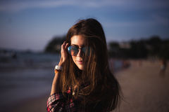 Close up portrait of slim lady in pink t-shirt and sunglasses near big stone at rock beach sea ocean shore. Royalty Free Stock Photography