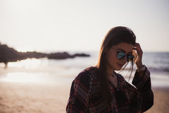 Close up portrait of slim lady in pink t-shirt and sunglasses near big stone at rock beach sea ocean shore. Royalty Free Stock Photos