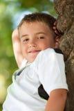 Portrait of cute boy resting in tree. Stock Image