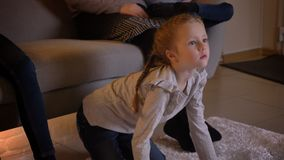 Close-up portrait of small caucasian girl with braids watching movie attentively and pointing finger on it with her stock footage