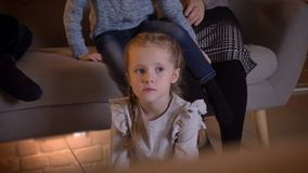 Close-up portrait of small caucasian girl watching movie attentively and changing her seat with another girl in cosy stock video footage